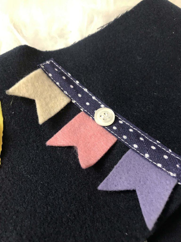 bandeirinhas de feltro de festa junina para decorar o colete infantil.